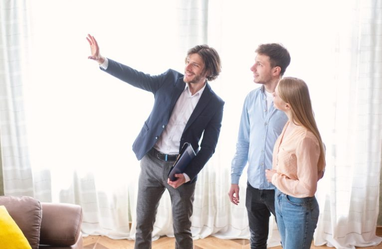 Millennial couple with cheerful real estate agent visiting house for sale